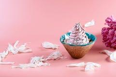 在桃红色口气的美丽如画的静物画,有白色瓣中介子围拢的乳脂状的蛋糕的装饰板材,附近是一朵桃红色花, 库存照片