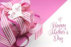 在桃红色和白色背景与样品文本和拷贝空间的美丽的桃红色礼物这里您的文本的为母亲节 库存图片