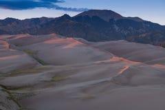 在桃红色和紫色日落光概述的沙丘在伟大的沙丘国立公园,支持落矶山 免版税库存图片