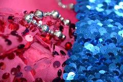 在桃红色和蓝色织品的衣服饰物之小金属片 免版税图库摄影