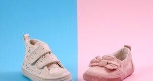 在桃红色和蓝色背景的儿童、男孩和女孩鞋子 免版税库存照片