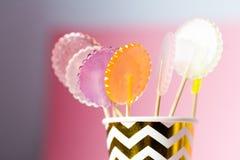 在桃红色和蓝色背景的多彩多姿的棒棒糖在纸奖杯 库存照片