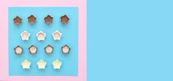 在桃红色和蓝色背景的巧克力果仁糖 库存照片