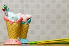 在桃红色和蓝色锥体的蓝色和桃红色蛋白甜饼用在木桌白色背景的杯形蛋糕,绿色和黄色棍子 图库摄影