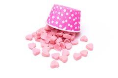 在桃红色圆点纸杯的落的心脏糖果 免版税图库摄影