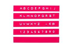 在桃红色塑料磁带上的压印的字母表 库存照片