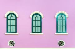 在桃红色墙壁上的三个绿色被成拱形的窗口 库存照片