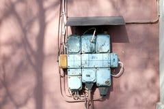 在桃红色墙壁上的葡萄酒保险丝箱子 库存照片