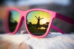 在桃红色太阳镜的激动的女孩剪影 库存照片