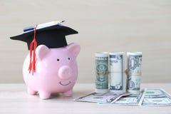 在桃红色存钱罐的毕业帽子有在木背景,教育概念的攒钱的钞票的 库存图片