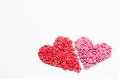 在桃红色心脏旁边的红色心脏由小装饰心脏做成在白色背景,在底部的焦点 欢乐背景为 免版税库存图片
