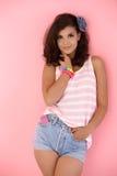在桃红色性感的微笑的墙壁的女孩 免版税图库摄影