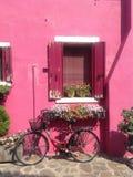 在桃红色房子附近的俏丽的自行车在Burano海岛上 库存图片