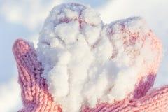 在桃红色手套的雪 免版税库存照片
