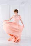 在桃红色晚礼服飞行的妇女跳舞在风 挥动的织品,时尚射击 库存照片