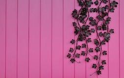 在桃红色木墙壁上的人造花 库存照片