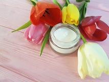 在桃红色木背景的化妆奶油色withbeauty湿气保护郁金香 免版税图库摄影