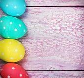 在桃红色木背景的复活节彩蛋 免版税库存图片