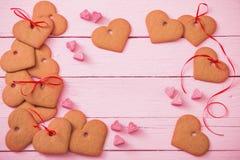在桃红色木背景的曲奇饼心脏 库存图片