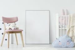在桃红色椅子的长毛绒玩具和在儿童` s室内部的蓝色枕头 库存图片