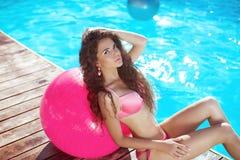 在桃红色比基尼泳装的美好的性感的妇女模型有pilates fitball的p 免版税图库摄影
