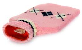 在桃红色毛线衣的一个热水袋有白色和黑样式的 免版税库存照片