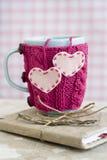 在桃红色毛线衣的蓝色杯子有站立在笔记本的心脏的 免版税库存图片