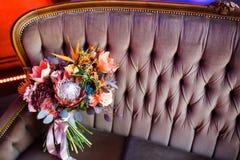 在桃红色沙发的美丽的婚礼花束 免版税库存图片