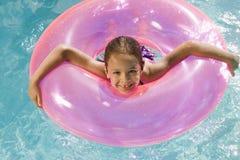在桃红色浮游物管里面的女孩在水池 免版税库存图片
