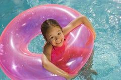 在桃红色浮游物管里面的女孩在水池 免版税图库摄影