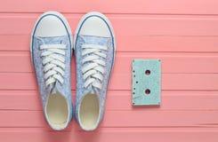 在桃红色淡色背景的卡型盒式录音机和运动鞋鞋子 库存图片