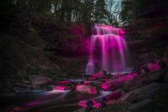 在桃红色照亮的瀑布 免版税库存照片