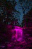 在桃红色照明的瀑布 库存图片