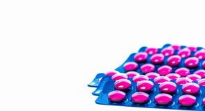 在桃红色片剂药片的异丁苯丙酸在与拷贝空间的白色背景隔绝的蓝色天线罩包装包装 安心痛苦的异丁苯丙酸 库存照片
