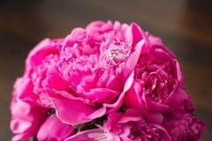 在桃红色牡丹花束的一个婚戒  婚姻照片概念的桃红色牡丹花束  免版税库存照片