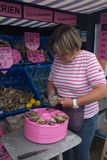 在桃红色牡蛎街道商店前面的妇女在康卡尔,法国 图库摄影