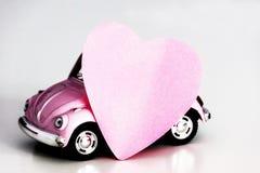 在桃红色玩具汽车的桃红色心脏 图库摄影