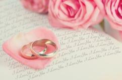 在桃红色玫瑰花瓣的金黄圆环在被打开的书 图库摄影
