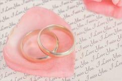 在桃红色玫瑰花瓣的金黄圆环有情书的 免版税库存照片