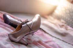 在桃红色用花装饰的床上的女孩时髦鞋子 免版税图库摄影