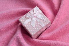 在桃红色的一个小礼物盒与一把小弓在软和毛茸的浅粉红色的羊毛织品毯子说谎与很多安心折叠的 免版税库存图片