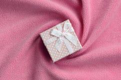 在桃红色的一个小礼物盒与一把小弓在软和毛茸的浅粉红色的羊毛织品毯子说谎与很多安心折叠的 库存图片