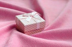 在桃红色的一个小礼物盒与一把小弓在软和毛茸的浅粉红色的羊毛织品毯子说谎与很多安心折叠的 免版税图库摄影