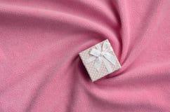 在桃红色的一个小礼物盒与一把小弓在软和毛茸的浅粉红色的羊毛织品毯子说谎与很多安心折叠的 免版税库存照片