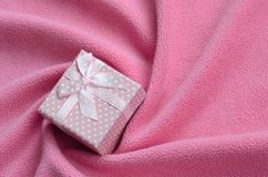 在桃红色的一个小礼物盒与一把小弓在软和毛茸的浅粉红色的羊毛织品毯子说谎与很多安心折叠的 库存照片
