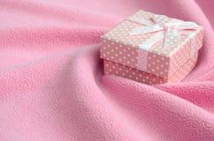 在桃红色的一个小礼物盒与一把小弓在软和毛茸的浅粉红色的羊毛织品毯子说谎与很多安心折叠的 图库摄影