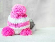 在桃红色的一只逗人喜爱的小的小猫编织了有大型机关炮睡眠的帽子在一张白色地毯 在帽子的逗人喜爱的睡觉全部赌注 库存照片
