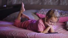 在桃红色睡衣打扮的逗人喜爱的白肤金发的小女孩在床和观看的动画片上在与智能手机 小孩女性孩子 股票视频