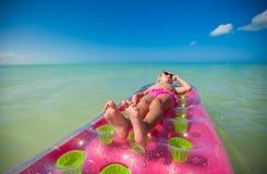 在桃红色空床上的小逗人喜爱的女孩晒日光浴  库存图片