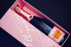 在桃红色箱子的香宾弗夫克利科罗斯瓶 库存照片